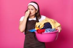 Houseworker castana che tiene il suo naso con una mano, avendo bacino rosa pieno degli oggetti cattivo odorare dei vestiti, prova immagine stock libera da diritti