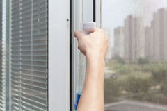 Houseworker clean plastic pvc window with detergent. Royalty Free Stock Photography