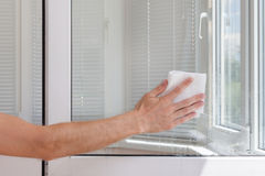 Houseworker clean plastic pvc window with napkin. Stock Photography
