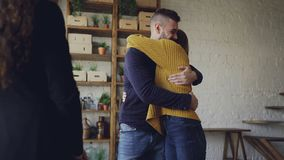 Housing agent is giving keys to buyers of new apartment, happy husband and wife are hugging and kissing, man is shaking. Housing agent is giving keys to excited stock footage