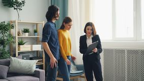 Housing agent talking to cheerful clients showing papers indoors in apartment. Professional housing agent is talking to cheerful clients showing papers stock footage