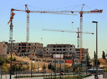 Housing Construction. Houses under construction with cranes against blue sky in Western Jerusalem in Israel Royalty Free Stock Image