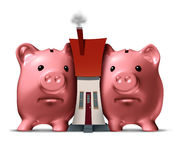 Housing Crunch. And home crisis concept as two piggy banks putting the squeeze on a family house as an economic symbol of feeling financial pressure and finance Royalty Free Stock Photos