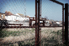 Housing England fence social. Social housing with fence and wasteland. Old metal gate to field with houses in background Royalty Free Stock Photos