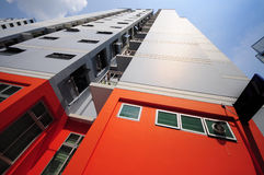 Housing Estate. A wide angle photo taken on a block of flats in a housing estate with orange colored ground floor stock photos