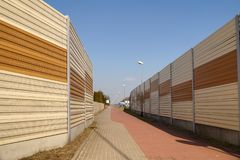 A housing estate protected against noise from the street using sound-absorbing barriers. Protective walls, acoustic panels. Protective walls, acoustic panels. A stock photo