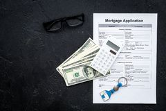 Housing loan. Draw up a mortgage. Mortgage application near keychain in shape of house and money on black background top. View royalty free stock images