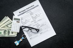Housing loan. Draw up a mortgage. Mortgage application near keychain in shape of house and money on black background top. View royalty free stock photo