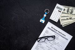 Housing loan. Draw up a mortgage. Mortgage application near keychain in shape of house and money on black background top. View stock photo