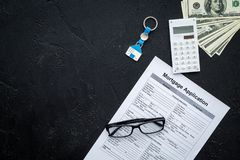 Housing loan. Draw up a mortgage. Mortgage application near keychain in shape of house and money on black background top. View royalty free stock photography