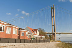 Housing next to a large suspension bridge Stock Photo