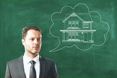 Housing, real estate and future concept. Young european businessman with abstract house sketch in thought cloud drawn on chalkboard background. Housing, real stock photo