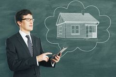 Housing, real estate and tomorrow concept. Young european businessman with abstract house sketch in thought cloud drawn on chalkboard background. Housing, real stock photos