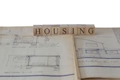 Housing written on wooden blocks on house extension building plans blueprints. With a white background stock image