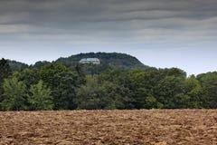 Houska castle in Czech Republic, Bohemia, Europe. State caste, hiden in green forest, dark grey clouds. Tower house in landscape. Stock Photo