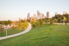 Houston Downtown Sunset from Eleanor. Downtown Houston at sunset from Eleanor Tinsley Park, grassy green park lawn, curved pathway with people walking, biking royalty free stock images