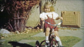HOUSTON, TEXAS 1953: Blonde cute little girls first tricycle ride around the backyard. stock footage