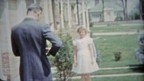 HOUSTON, TEXAS 1953: Meisje die haar eerste katholieke kerkgemeenschap kussende oma vieren stock footage