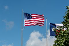 Houston, Texas USA - June 15: American flag fluttering in the wind. The US and Texas flag fluttering in the wind with clouds in the background stock images