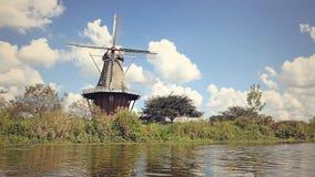 Hout en baksteen ouderwetse Nederlandse Windmolen langs een kanaal stock foto