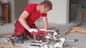 Houtbewerking in het huis - een jong professioneel mannetje zet een vloer van het pijnboomhout op stock footage