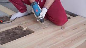 Houtbewerking in het huis - een jong professioneel mannetje zet een vloer van het pijnboomhout op stock videobeelden