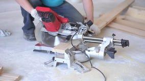 Houtbewerking in het huis - een jong professioneel mannetje zet een vloer van het pijnboomhout op stock video