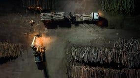 Houtbewerkingsfabriek Het laden van het bos in de vrachtwagen Nacht luchtfotografie stock afbeelding