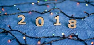 Houten aantallen die het aantal 2018 en Kerstmislichten op a vormen Stock Foto's