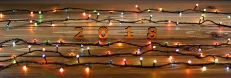 Houten aantallen die het aantal 2018 en Kerstmislichten op a vormen Stock Afbeeldingen