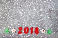 Houten aantallen die het aantal 2018, voor het nieuwe jaar en de sneeuw op een grijze concrete achtergrond vormen Stock Afbeelding