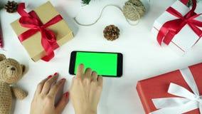Houten achtergrond. Hoogste mening. Zwarte smartphone met het groene scherm die op de lijst met de decoratie van de Kerstmisvakant stock videobeelden