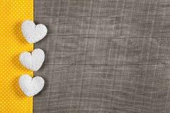 Houten achtergrond met drie witte en gele harten op houten B Stock Foto