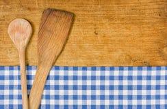 Houten achtergrond met een geruit tafelkleed en houten lepel stock fotografie