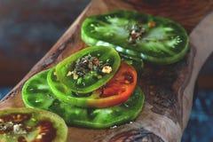 Houten achtergrond van olijfbomen en de cirkels van gehakte groene ingelegde tomaten met kruiden en knoflook Kopieer Stock Foto's