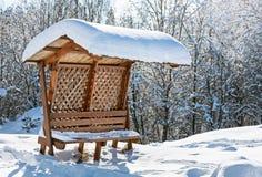 Houten afbaardende bank die door sneeuw wordt behandeld Stock Foto's