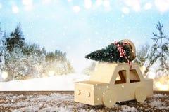 Houten auto die een Kerstmisboom dragen Stock Fotografie