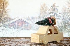 Houten auto die een Kerstmisboom dragen Stock Foto