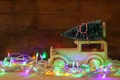 Houten auto die een Kerstmisboom op rustieke lijst dragen Stock Foto's