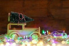 Houten auto die een Kerstmisboom op rustieke lijst dragen Royalty-vrije Stock Foto