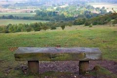 Houten bank die Engels platteland overziet stock afbeeldingen