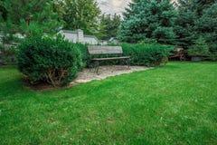 Houten bank in een mooie parktuin Royalty-vrije Stock Afbeeldingen