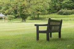 Houten bank onder een grote boom die zich op een grasgebied bevinden in een park grote tuin Royalty-vrije Stock Afbeelding