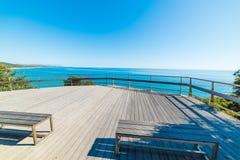 Houten bank op een panoramisch terras door het overzees in de kustlijn van Sardinige stock foto