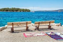 Houten banken en handdoeken op het strand, Solta, Kroatië Stock Afbeeldingen