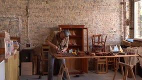 Houten beeldhouwer aan het werk in workshop stock video