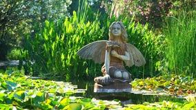 Houten beeldhouwwerk van een fee in een vijver met waterlelies stock videobeelden