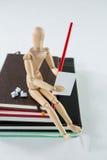 Houten beeldjezitting op een stapel van boeken die op een document schrijven royalty-vrije stock afbeeldingen