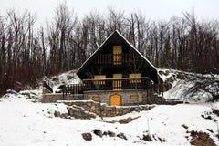 Houten bergsneeuw behandeld plattelandshuisje met steenstichting Royalty-vrije Stock Afbeelding