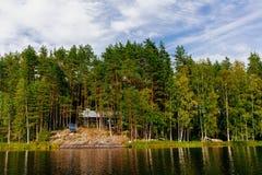 Houten blokhuis bij het meer in de zomer in Finland Stock Afbeelding